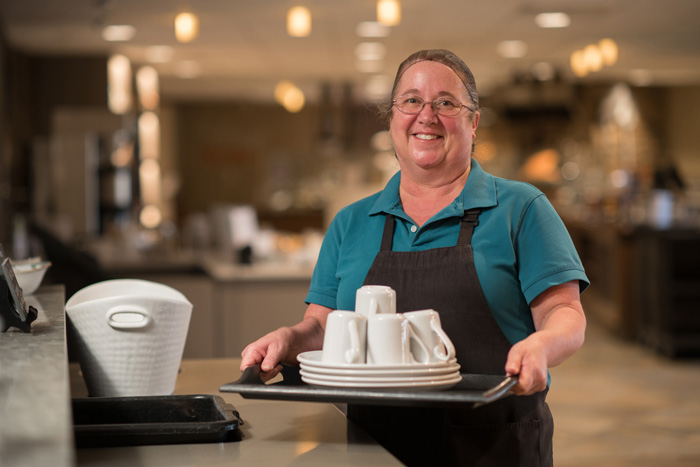 Female employee with a tray of mugs and plates