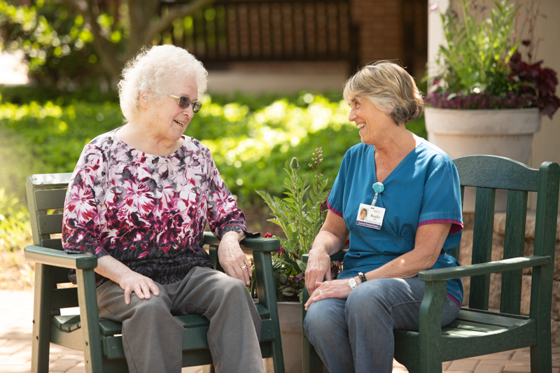 Female resident talking outside with female health care worker
