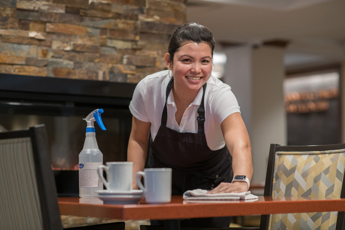 Female employee cleaning a dining table